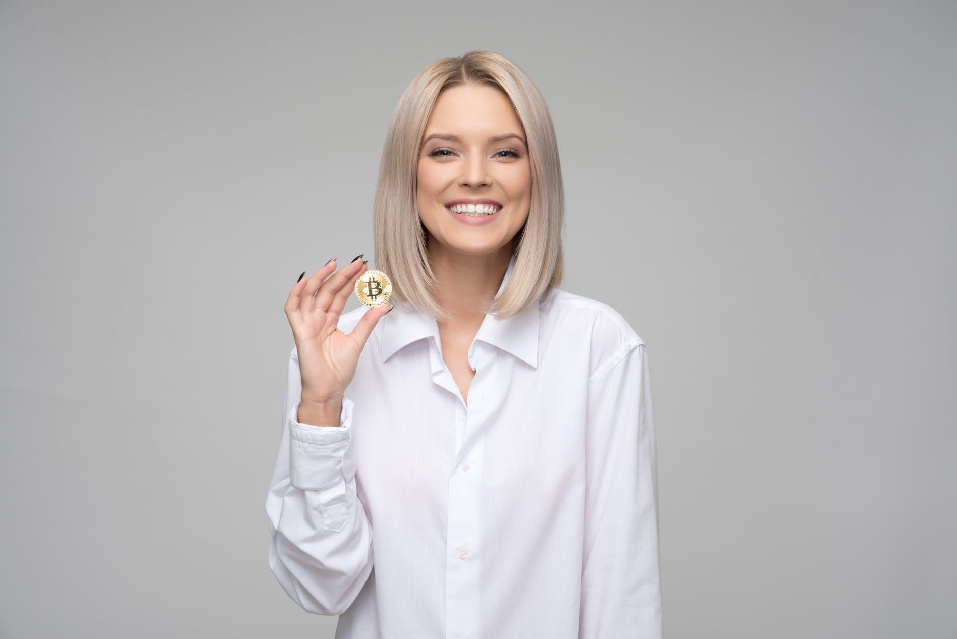 women wearing white long sleeved collared shirt holding bitcoin